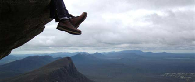 person hanging their feet over the edge of a cliff